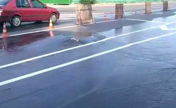 Струя воды пробила асфальт на новой дороге - фото 1